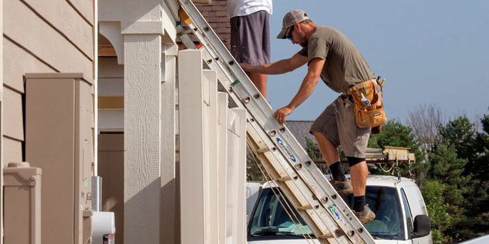epcon construction franchise workers on ladder outside