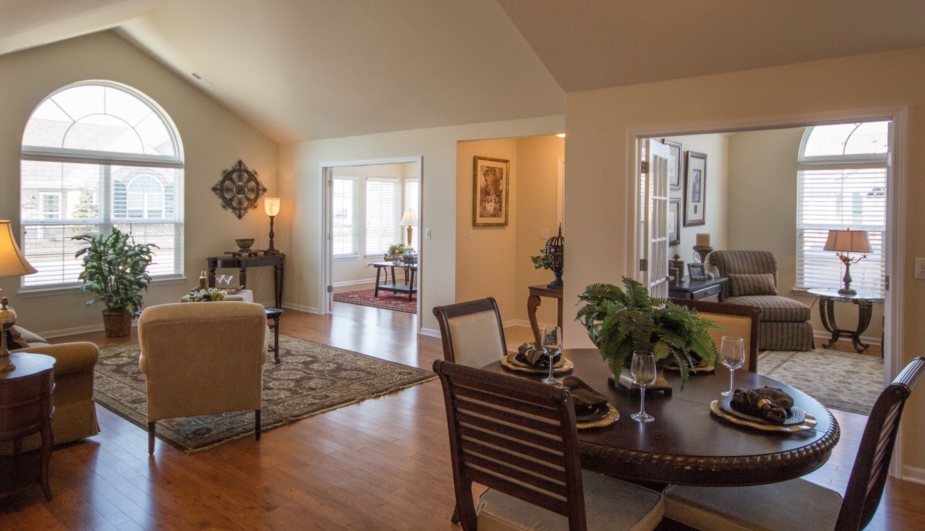Eye-level view of an open-style living room and breakfast area with an alcove in between an office and bonus room.