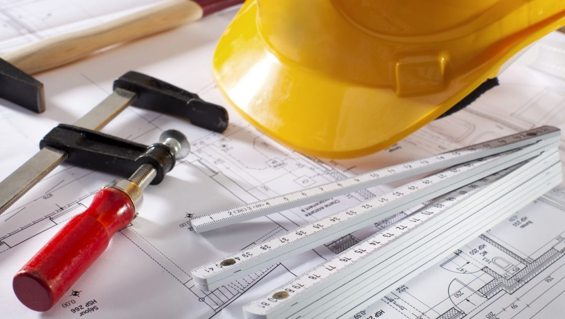 Hard hat and tools laying on a blue print