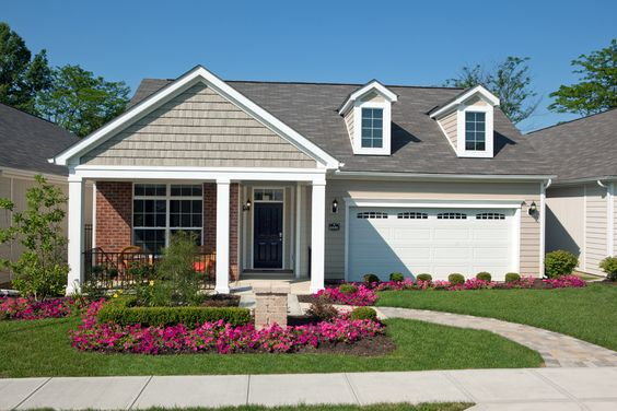 A one-story home features a front yard landscaped with fuchsia flowers and low bushes.