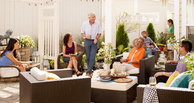 A group of middle-aged and senior adults enjoy a low-key party in the patio area of an Epcon home.