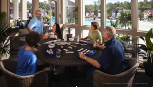 Residents socialize and play games on the screened-in patio of an Epcon clubhouse.