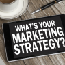 A tablet reading WHAT'S YOUR MARKETING STRATEGY? sitting on a wooden table near a pen and cup of coffee